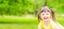 Portrait Of A Joyful Little Girl With Syndrome Down In A Summer Park. Empty Space For Text
