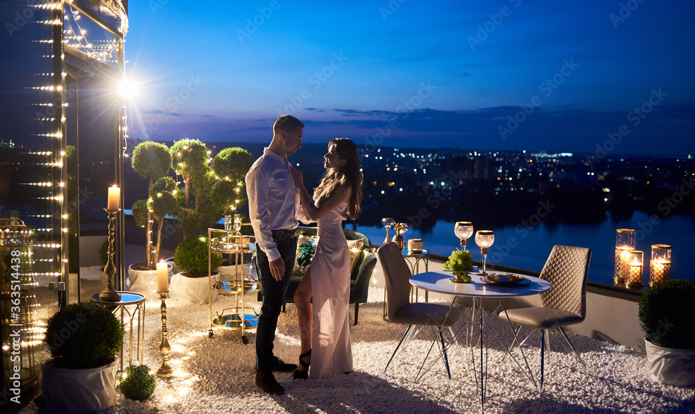 Fototapeta Young woman in elegant evening dress standing with boyfriend on rooftop terrace with night cityscape on background. Stylish gentleman looking at charming girlfriend and smiling. Concept of love.