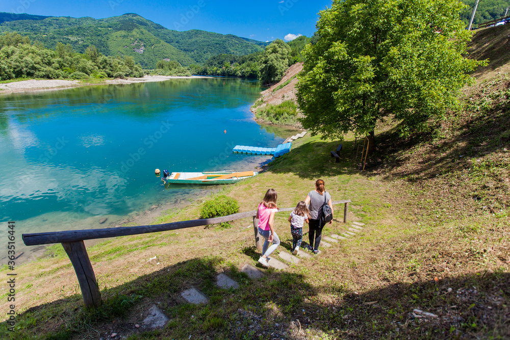 Fototapeta Family enjoy nature on summer day by river, beautiful nature , wooden boats on the water