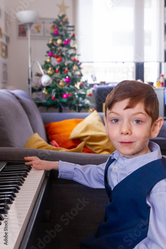Portrait Of Boy Sitting Playing Piano At Home In Christmas Wallpaper Mural