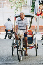 Senior Man Riding Pedicab On Road In City