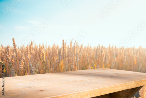 Modne obrazy  empty-wooden-deck-table-over-wheat-field-with-sunset-or-sunrise-ready-for-product-montage