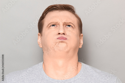 Fotografie, Tablou Portrait of funny goofy man puffing out his cheeks and pouting lips