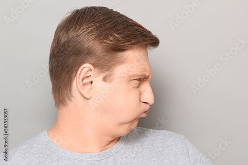 Photo Portrait of funny goofy man puffing out his cheeks and pouting lips