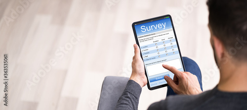 Man Filling Online Survey Form On Digital Tablet