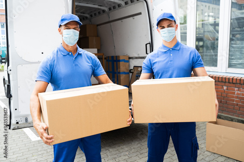 Blue Delivery Men Unloading Package From Truck
