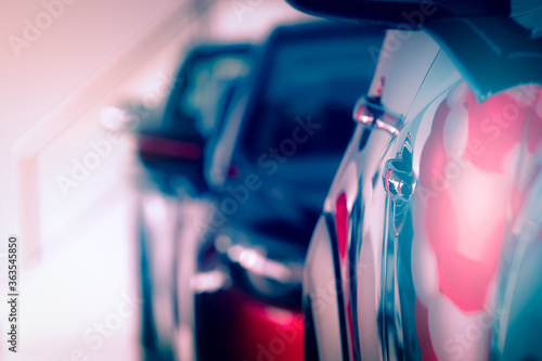 Obraz Blurred red car parked in modern showroom. Car dealership and auto leasing concept. Automotive industry. Modern luxury showroom. New shiny car parked in a row. Electric automobile technology. - fototapety do salonu