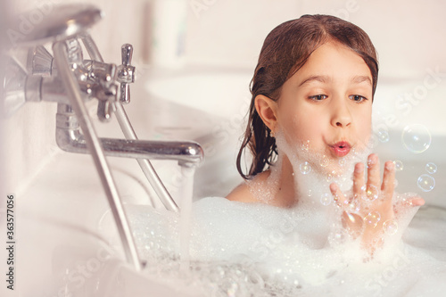 Fotografia The girl bathes and plays with foam in the bathroom
