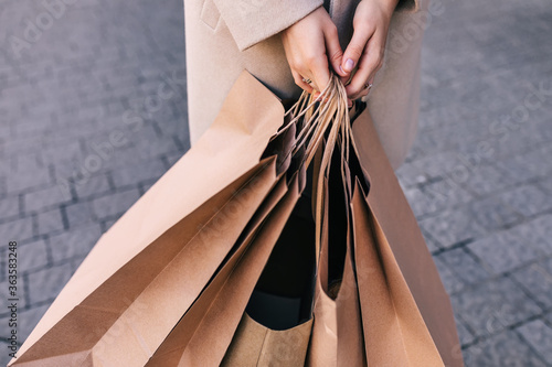 hand holds brown eco-friendly craft paper bag. Wallpaper Mural