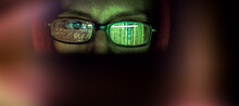 Hacker At Computer Data Reflecting In Eyeglasses