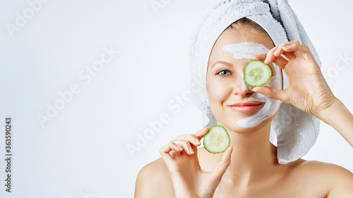 Fototapety, obrazy: Cosmetology, skin care, face treatment, spa and natural beauty concept. Woman with facial mask holds slices of cucumber.