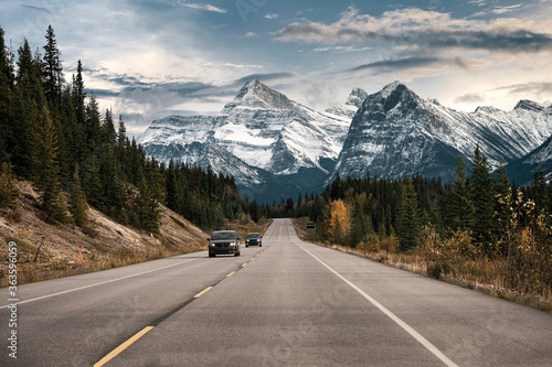 Fototapeta Car driving on highway with rocky mountains in Banff national park obraz
