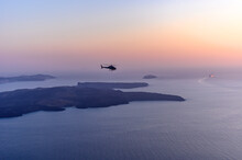 Helicopter Flying Over Sea Against Sky During Sunset In Santorini.