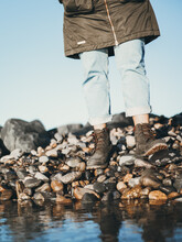 Low Section Of Person Standing On Pebble Stones By Lake