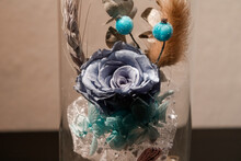 Artificial Rose Flower In A Glass Vase Decorated With Other Flowers And Plants