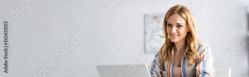Panoramic shot of smiling woman using laptop Billede på lærred