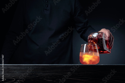 Fotografie, Obraz Alcoholic drink pouring from a bottle into a frosted glass with ice