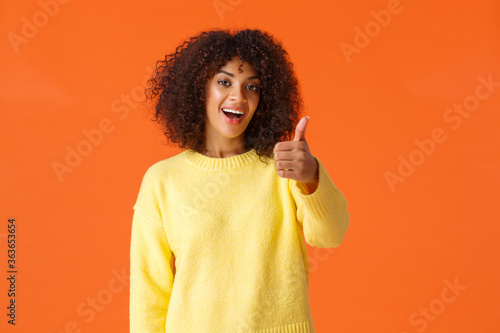 Cheerful outgoing modern african american woman with curly hair, showing thumb-u Canvas-taulu