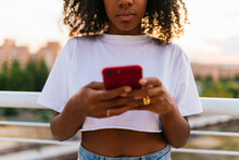 African Woman Holding A Mobile Phone Reading A Text Message