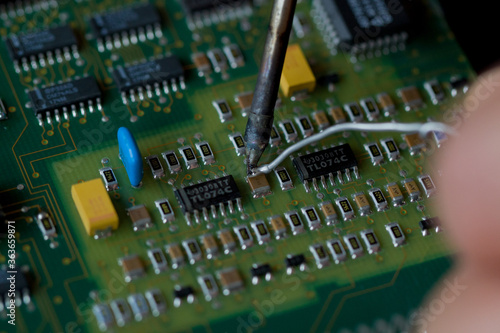 Obraz na plátně Soldering iron and solder close-up on the background of an electronic Board with microchips