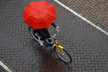 Biking In The Rain With Umbrella