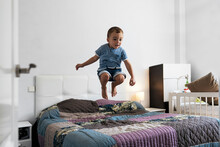 Boy Having Fun On Bed