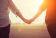 Leinwandbild Motiv Midsection Of Couple Holding Hands Against Sky During Sunset