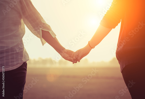 Fotografia Midsection Of Couple Holding Hands Against Sky During Sunset