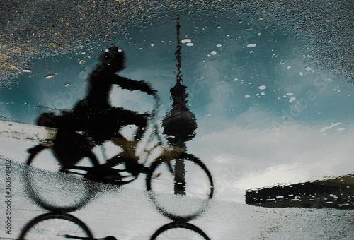Obraz na plátně Puddle Reflection Of Biker And Television Tower  In Berlin