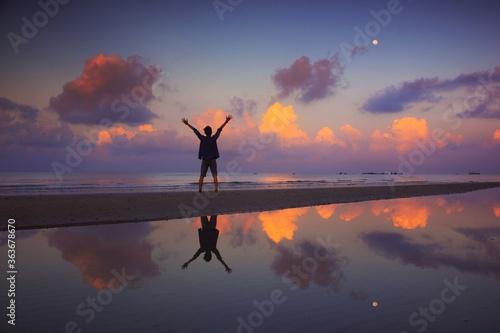 Fototapeta Silhouette Man Standing In Sea Against Sky During Sunset obraz