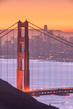 The San Francisco Skyline Behind The Golden Gate Bridge At Sunset