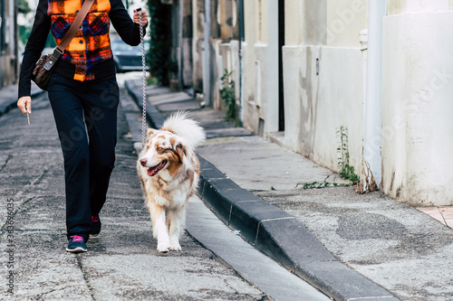 Photo Femme en train de promener son chien berger australien dans la rue