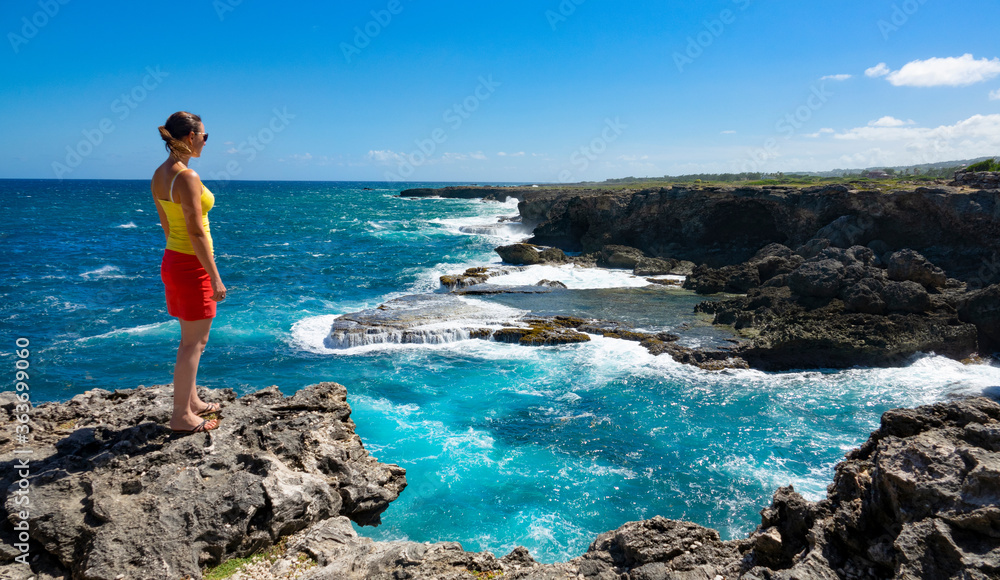 Fototapeta COPY SPACE: Female traveler stands on the edge of a cliff and observes the coast