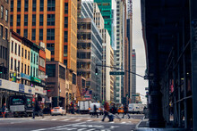 Street Amidst Buildings And People Crossing In City Of Manhattan