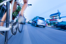 Low Section Of Person Riding Bicycle On City Against Sky
