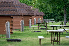 Rows Of Rustic Camping Cabins, With Water Pumps And Picnic Tables At A Campground