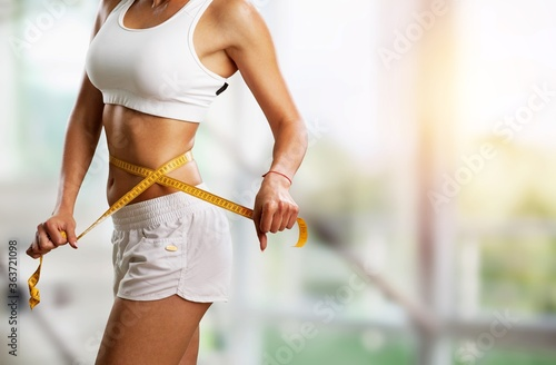 Obraz Young woman with the beautiful slim waist on background - fototapety do salonu