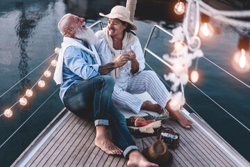 High Angle View Of Cheerful Couple Sitting On Boat At Sunset