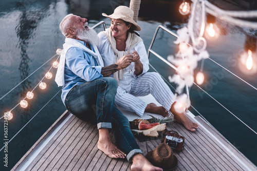 Photo High Angle View Of Cheerful Couple Sitting On Boat At Sunset