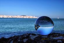 Crystal Ball On Rock At Beach Against Clear Blue Sky
