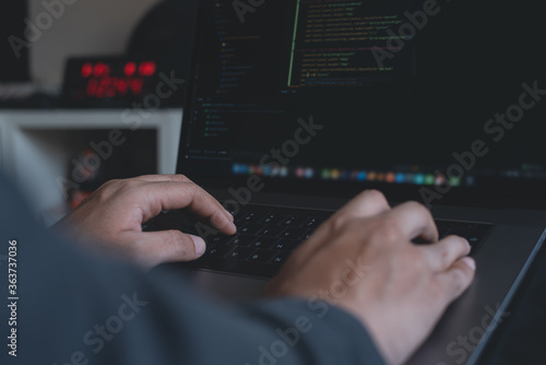 Fotografiet Programmer or software developer coding on laptop computer