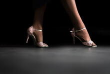Low Section Of Woman Wearing Heels Standing On Floor Against Black Background