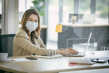 Business Woman Wearing Face Mask And Using Partition On Table For Protect Coronavirus Covid-19 Pandemic. Social And Business Distancing New Normal Lifestyle.