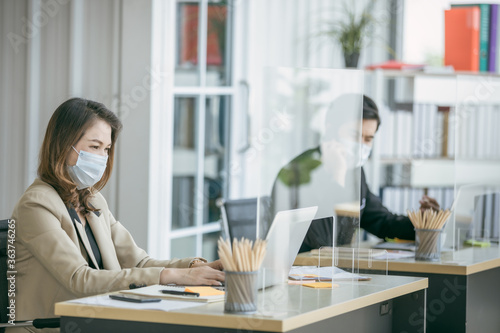 Fototapeta Business office working together at new normal social distance with table shield partition reduce infection of coronavirus covid-19 pandemic