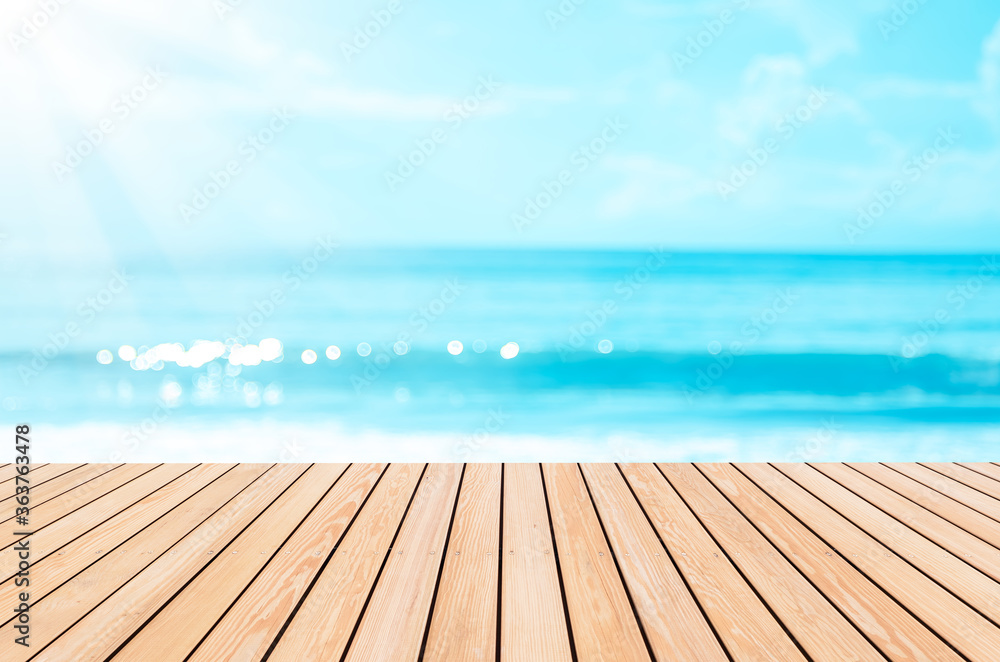 Fototapeta Blur tropical beach with bokeh sun light wave on empty old nature wood table abstract background.