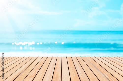 Canvastavla Blur tropical beach with bokeh sun light wave on empty old nature wood table abstract background