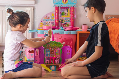 Siblings Playing With Toys While Sitting At Home Fototapet