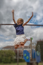 Low Angle View Of Girl With Arms Raised Jumping Against Cloudy Sky
