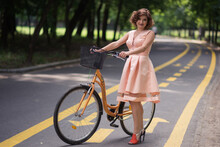 Portrait Of Woman With Bicycle On Road In City