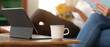 Digital tablet with keyboard and coffee cup on wooden coffee table in living room